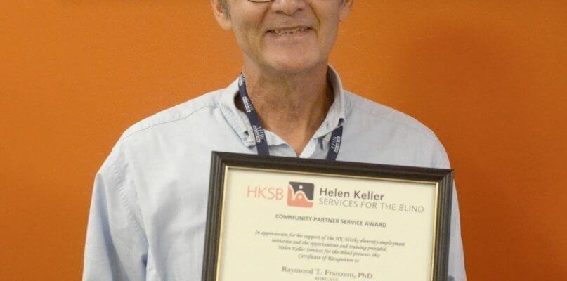 Dr. Raymond Franzem, Director of Internships, holding his Community Partner Service Award from Helen Keller Services for the Blind - Copy