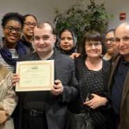 Ian Maiorca holds his award as he poses with his family and friends from Cyril Weinberg Adult Day Center