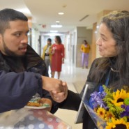 Artist, Jayson Valles shakes hands with Jodi Moies, Curator of Montefiore's Fine Art Program and Collection