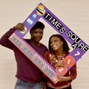 Leeann Washington and Comfort Madison of Church Avenue Day Habilitation pose in the transit themed photo booth