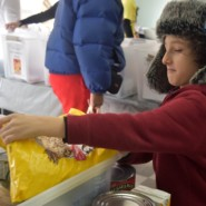 A young volunteer prepared a box of food to be distributed to those in need via Meals on Wheels