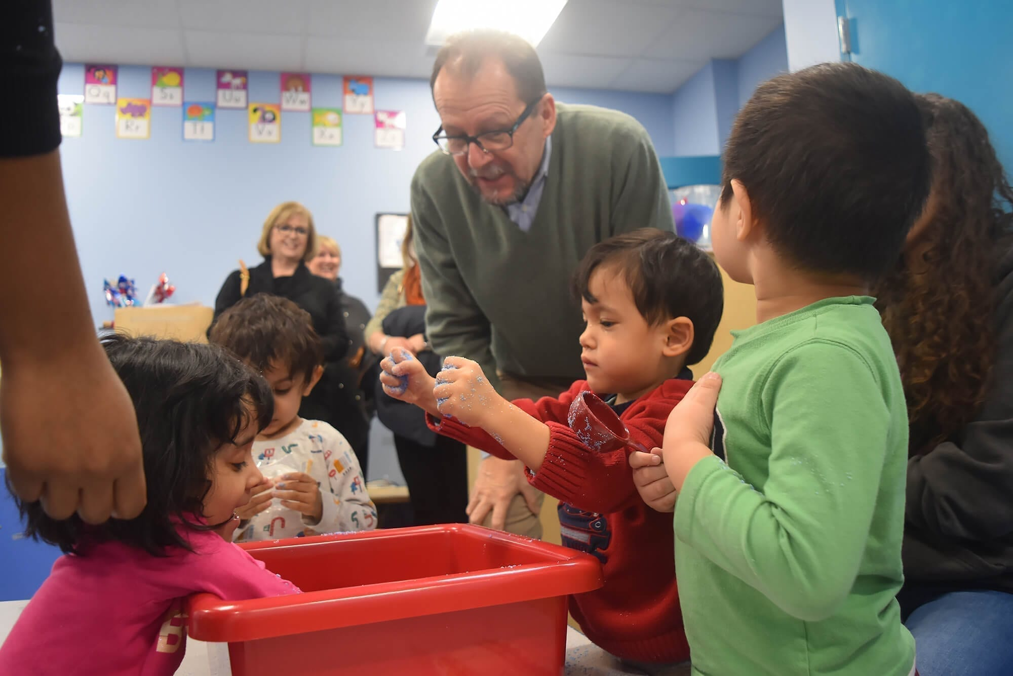 Diana Munson watches as AHRC NYC's CEO, Marco Damiani, engages with the children