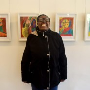 Devona Gamble puts on a big smile in front of several of her exhibited pieces