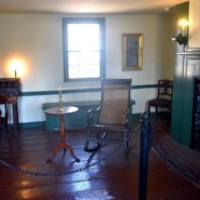 The interior of Edgar Allen Poe's cottage in the Bronx. The rocking chair on the right was used by the author.