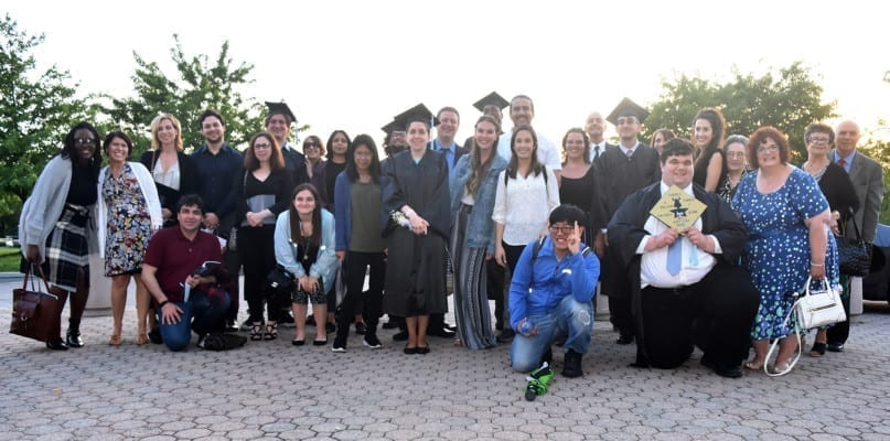 Graduates, staff members, and family members after the 2019 commencement ceremony at CSI