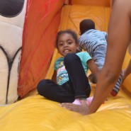 A child from Howard Haber ELC slides in for a safe landing on the bouncy castle slide at the school's Summer Carnival.
