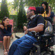 Alexandria Ocasio Cortez sepaks with artist and self advocate Abraham Roberts.