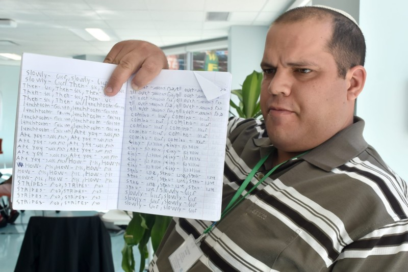 Shai Agai displays his perosnal notebook where he has been practicing his English by tranlsating words from his native Hebrew.
