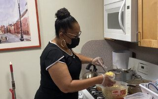 Theresa Williams Wiggins prepares lunch for the residents at Bloomberg Apartments.